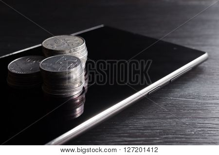 Stack of rupiah coin on smartphone showing it relation. Like business money making