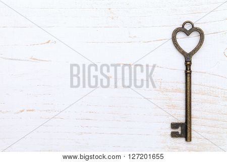 heart shaped vintage key on white wood background