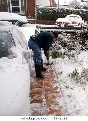 A Man Clearing The Snow From The Path
