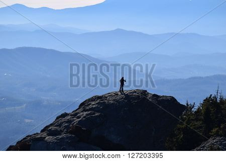 Silhouetted man reaching off towards blue mountains of North Carolina