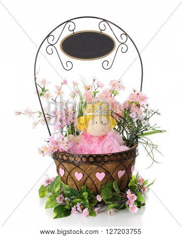 A doll with a queen's crown in a basket surrounded with pink blossoms and hearts.  From the handle hangs a blank sign for your message.  On a white basket.