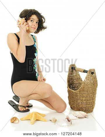 An attractive young teen in her swim suit listening to a conch shell with her collections basket and other shells nearby.  On a white background.