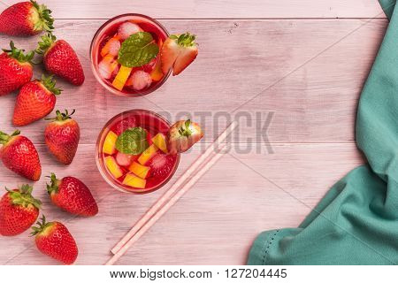 Refreshing summer drink with strawberry lemon and ice in glasses on the vintage wooden table. Top view with copy space.