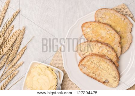Fresh bread wheat spike and homemade butter on wooden background. Top view with copy space.