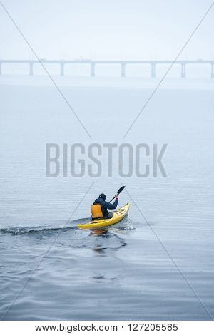 man paddles a yellow kayak on the river near the shore kayaking