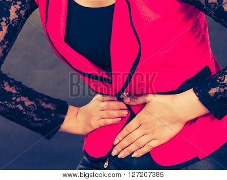 Sickness and diseases. Health problem concept. Young woman in red holding her hands on stomach belly because of strong terrible bad pain ache.