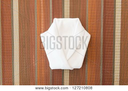White Napkin Folded Into A Shirt On Dinner Table