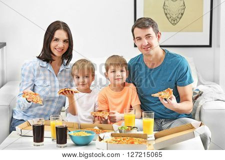 Happy family eating pizza on sofa all together