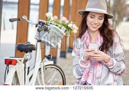 Happy girl watching media in a smart phone sitting in the street beside her bicycle