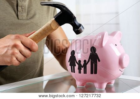Man with a hammer going to break the piggy bank, close up
