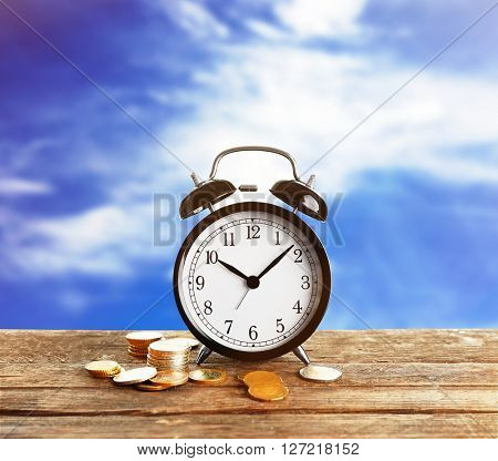 Alarm clock and money coins on wooden table, blue sky background