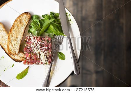 Tartare of beef with spinach on a white plate. Isolated on black.
