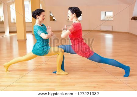 Two Young Women Do Yoga Indoors