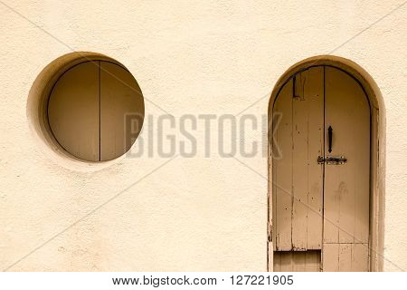 An adobe building with an arched doorway and a circle window.