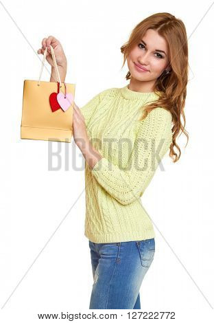 girl with shopping bag and hearts  dressed jeans and a green sweater posing in studio on white background