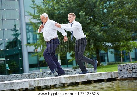 Businessman chasing senior CEO in front of the office