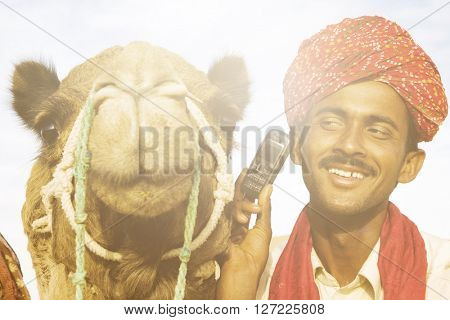 Asian Man and Camel in the Desert with Communications
