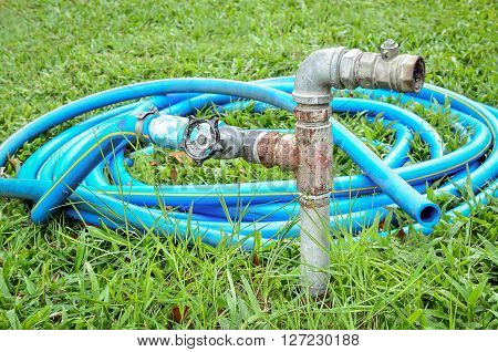 Old water valve with blue rubber water hose in the sunlight