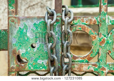 A green rusty lock on an iron door with a chain