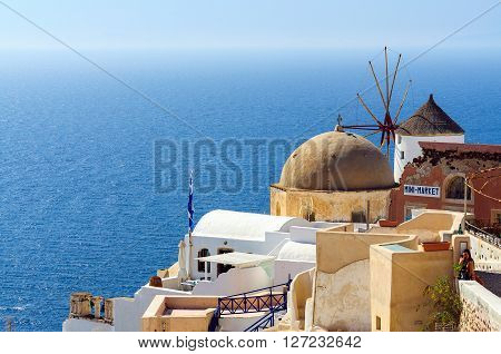 OIA, SANTORINI, GREECE- AUGUST 15, 2015: Traditional architecture with windmill of Oia town at sunny day, Santorini island, Greece