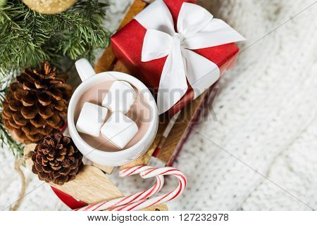 close-up of christmas time themed decorations by the tree: toy sled with hot chocolate filled cup and marshmallows nicely wrapped present candy canes and tree cones cozy knitted throw in the background