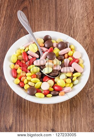 Colorful medical pills on teaspoon and tablets capsules or supplements for therapy on plate concept of treatment and health care