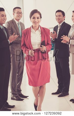 Smiling successful business lady walking along row of clapping colleagues
