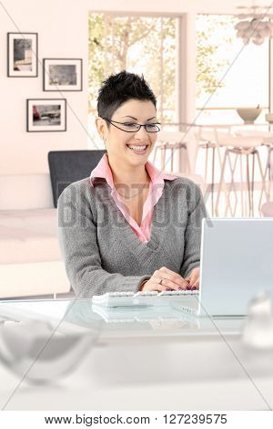Happy young casual caucasian businesswoman working at home on laptop computer, wearing glasses, sitting at desk, looking at screen, typing, doing business. Smiling.