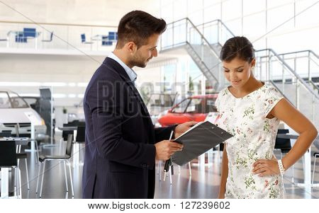 Young attractive casual caucasian woman at car dealership reviewing business papers. Male saloon sales manager wearing suit, clipboard in hand. Communication, looking down, smiling, hand on hip.