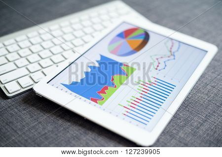 Business charts and diagrams on digital tablet