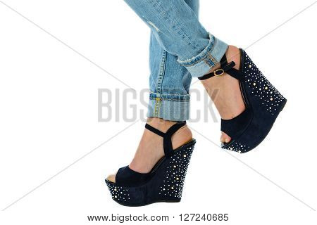 girl in jeans and high heels with studs and rhinestones on white background