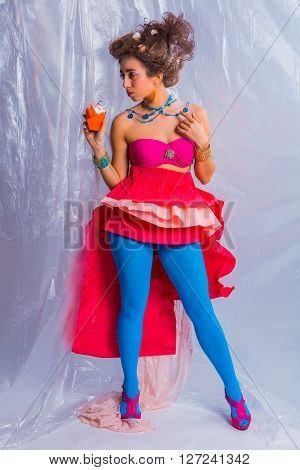 Beautiful girl in bright clothes and make up with colorful cherry muffin.