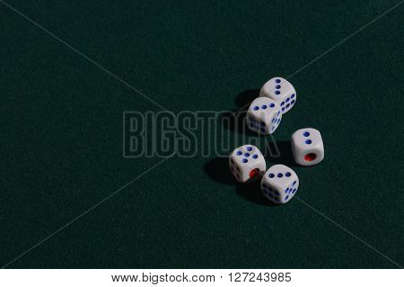 Five dice for the game of dice on a green cloth