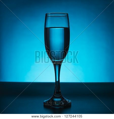 champagne glass with water isolated on blue
