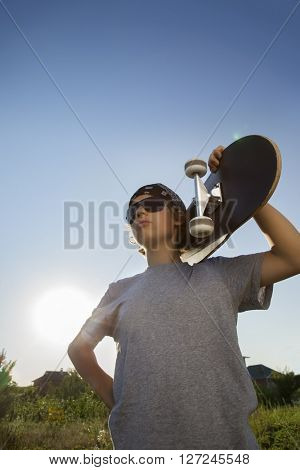 Young boy with skateboard in hand against the sky