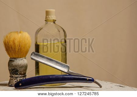 A sharp straight razor brush and cologne aftershave