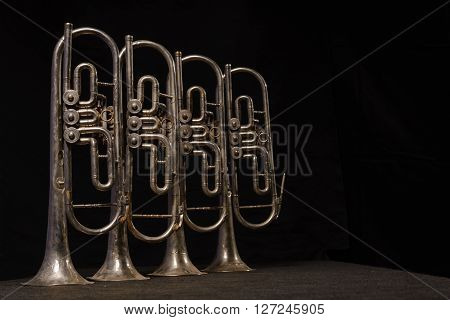 Four old brass wind instrument stand on a table on a black background