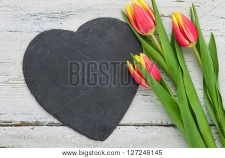 Red Tulips On A White Background With A Heart-shaped Sign