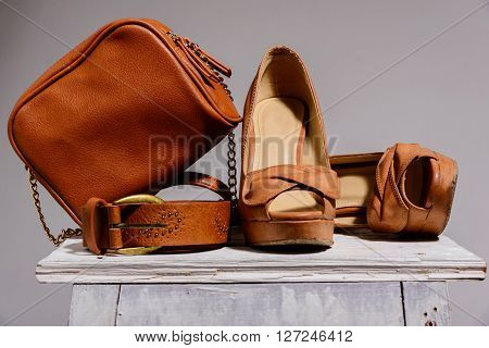 brown female bag with shoes and belt isolated on gray background