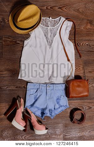 Set of feminine summer clothing on wooden background