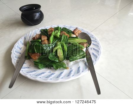 Stir fried kale vegetable with crispy pork over steamed rice in Thai restaurant