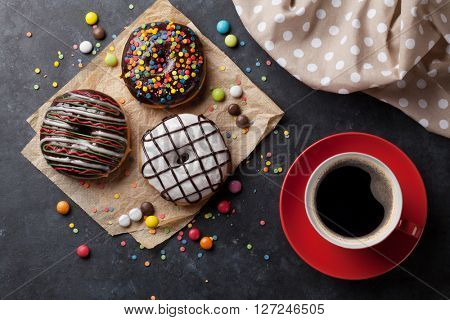 Donuts and coffee on stone table. Top view