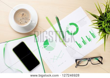 Office desk workplace with charts, phone, coffee cup, plant and notepad on wooden table. Top view with copy space