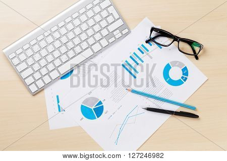 Office desk workplace with pc, charts and glasses on wooden table. Top view