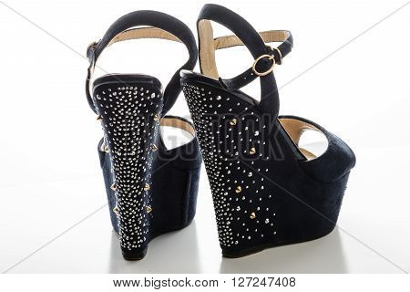 Stylish women's blue sandals with high heels with studs on a white background.