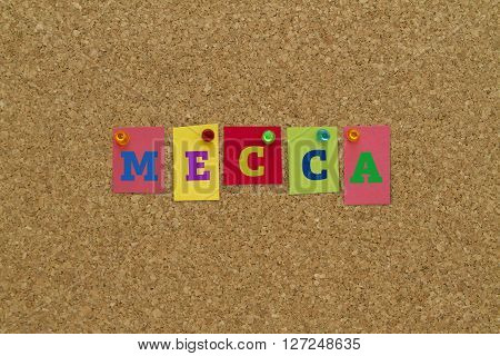 Mecca written on colorful notes pinned on cork board.