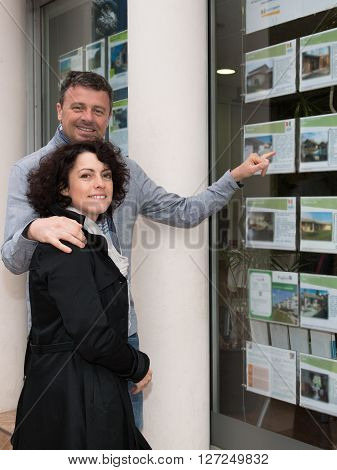 Couple Looking At Window Display At Real Estate Office