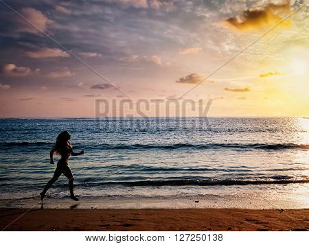 Healthy sporty fitness fit life concept - beautiful athletic woman running along sea on the beach in the morning