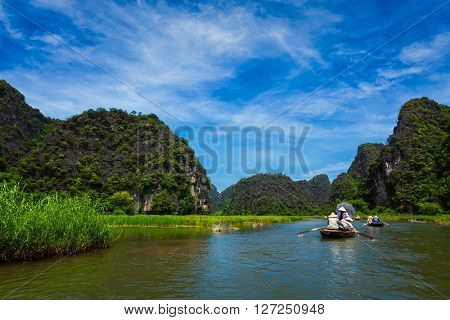 Tourists on boats in Tam Coc-Bich Dong Ngo Dong river in popular tourist destination near Ninh Binh, Vietnam