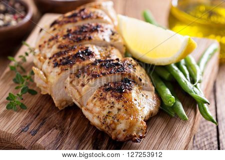 Grilled chicken on a cutting board with thyme and green beans
